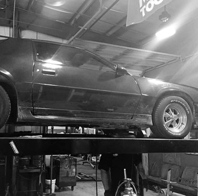 car on lift in service bay